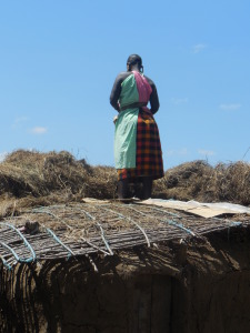 Masai woman reparing her home